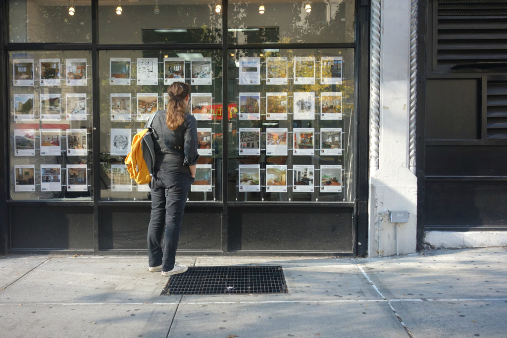 woman standing in front of real estate brochures